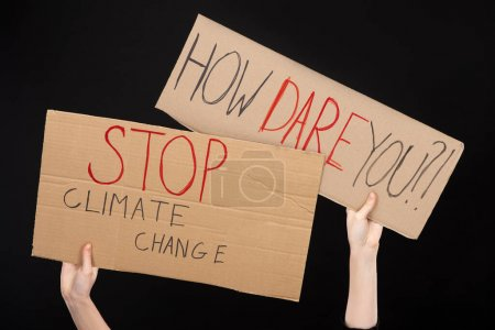 Photo for Cropped view of woman holding placards with how dare you and stop climate change lettering isolated on black, global warming concept - Royalty Free Image