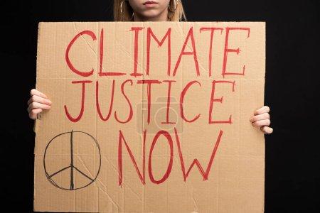 Foto de Una visión parcial de la mujer rubia que mantiene pancartas con la justicia climática ahora se aleja del concepto de calentamiento global y negro. - Imagen libre de derechos