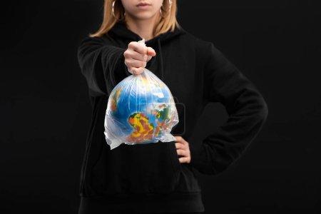 Foto de Vista parcial de la mujer con la mano extendida sosteniendo bolsa de plástico con globo aislado en negro, concepto de calentamiento global - Imagen libre de derechos