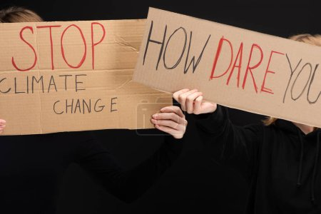 Photo for Cropped view of blondes with placards with stop climate change and how dare you lettering isolated on black, global warming concept - Royalty Free Image