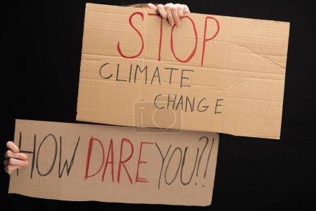 Photo pour Vue agrandie d'une femme avec des pancartes avec l'arrêt des changements climatiques et comment oser laisser des lettres isolées sur le concept noir de réchauffement planétaire - image libre de droit