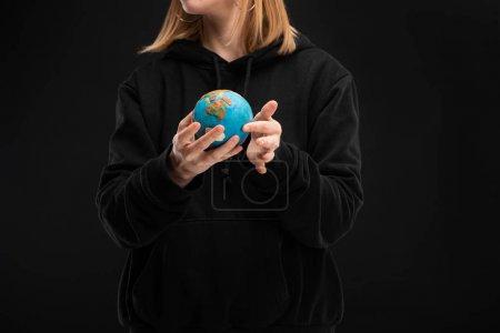 Photo pour Vue recadrée d'une femme tenant un globe de plasticine isolé sur un concept noir de réchauffement climatique - image libre de droit