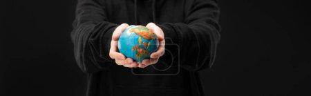 Foto de Visión panorámica de la mujer que sostiene el planeta de la plastilina aislada en el concepto de calentamiento global y negro - Imagen libre de derechos