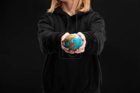 Foto de Vista recortada de la mujer con las manos extendidas sosteniendo globo de plastilina aislado en negro, concepto de calentamiento global - Imagen libre de derechos