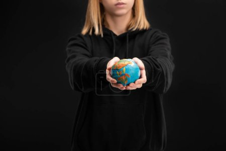 Partial view of woman with outstretched hands holding plasticine globe isolated on black, global warming concept