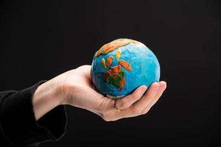 Photo pour Vue partielle d'un globe de plasticine dans une main de femme isolée sur un concept noir de réchauffement global - image libre de droit
