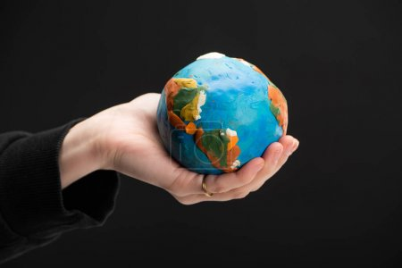 Cropped view of plasticine globe in female hand isolated on black, global warming concept