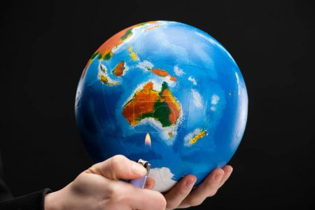 Cropped view of woman holding lighter and globe isolated on black, global warming concept