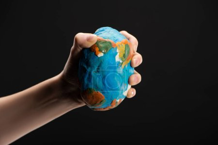 Photo for Partial view of woman compressing plasticine globe in hand isolated on black, global warming concept - Royalty Free Image