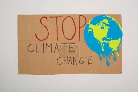 Widok z góry tabliczki z pomalowanym globusem i powstrzymanie literowania zmian klimatu na szarym tle, koncepcja globalnego ocieplenia
