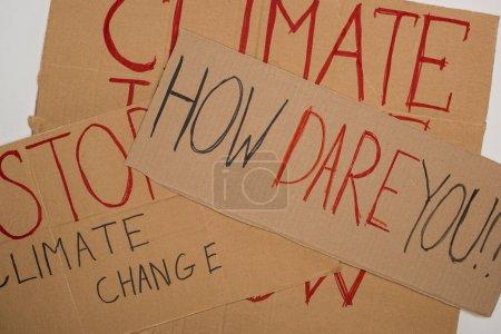 Photo pour Vue d'ensemble des pancartes avec comment oser, stopper le changement climatique, la justice climatique maintenant sur le gris, concept de réchauffement planétaire - image libre de droit
