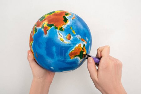Cropped view of woman setting to fire globe on white, global warming concept