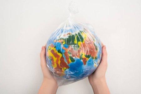 Photo pour Vue recadrée de la femme tenant un sac en plastique avec globe sur blanc, concept de réchauffement climatique - image libre de droit