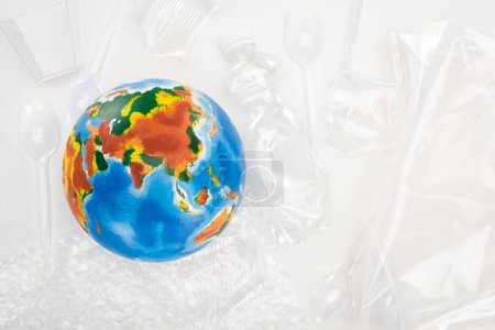 Photo for Top view of globe on plastic garbage on white background, global warming concept - Royalty Free Image