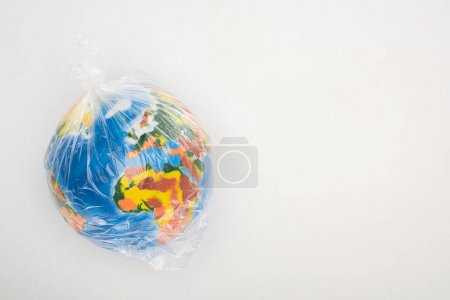 Top view of globe in plastic bag on white background, global warming concept