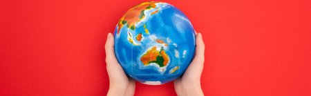 Panoramic view of woman holding globe isolated on red, global warming concept
