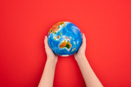 Cropped view of woman holding globe on red background, global warming concept