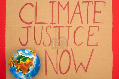 Foto de La visión superior del globo y la pancarta con justicia climática ahora se basa en el fondo rojo, el concepto de calentamiento global. - Imagen libre de derechos