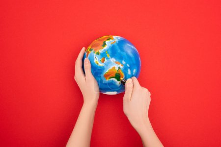 Cropped view of woman setting to fire globe on red, global warming concept