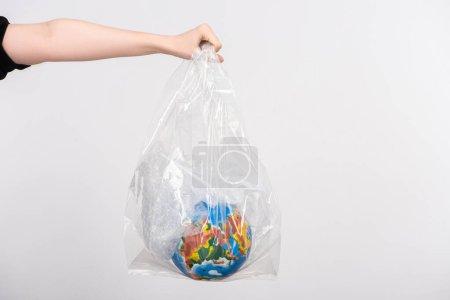 Photo pour Vue partielle de la femme avec globe à main tendue dans un sac en plastique isolé sur blanc, concept de réchauffement climatique - image libre de droit