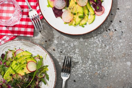 Photo for Top view of fresh radish salad with greens and avocado served on plates on grey concrete surface with water, cutlery and napkins - Royalty Free Image