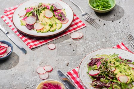Photo for Fresh radish salad with greens and avocado in plates served on napkins with cutlery near ingredients in bowls on grey concrete surface - Royalty Free Image