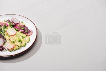 Photo pour Salade de radis frais avec légumes verts et avocat sur la surface grise - image libre de droit