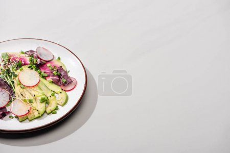 Photo for Fresh radish salad with greens and avocado on grey surface - Royalty Free Image