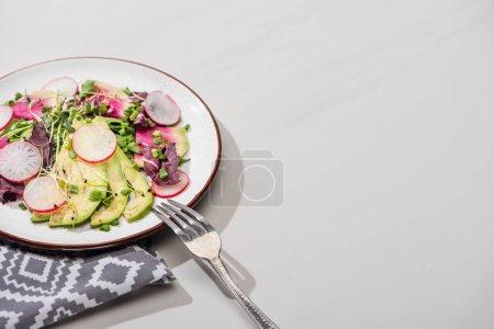 Foto de Ensalada de rábano fresca con verdura y aguacate en superficie gris con nafkin y tenedor. - Imagen libre de derechos