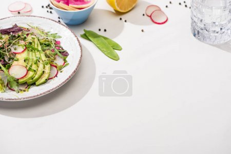 Photo for Fresh radish salad with greens and avocado on white surface with ingredients in bowls and water - Royalty Free Image