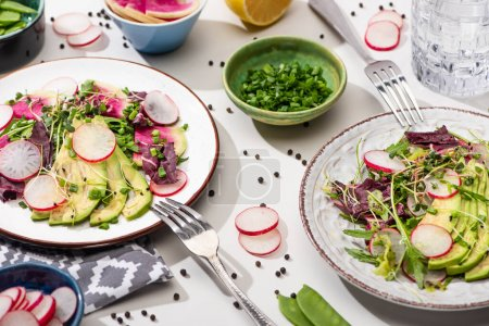 Photo for Fresh radish salad with greens and avocado on plates on white surface with ingredients in bowls and water - Royalty Free Image