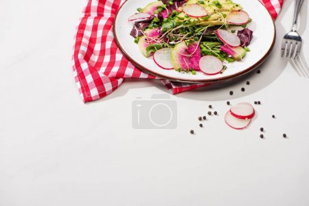 Photo for Fresh radish salad with greens and avocado on plate on white surface with napkin and fork - Royalty Free Image