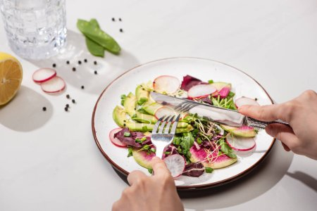 Photo for Cropped view of woman eating fresh radish salad with greens and avocado on white surface with water - Royalty Free Image