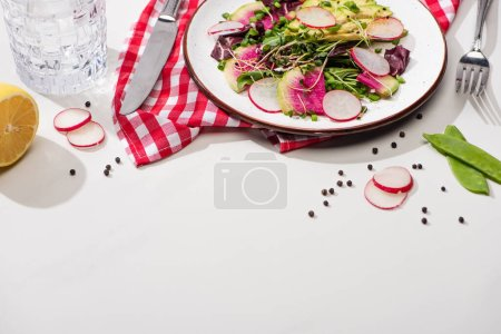 Photo for Fresh radish salad with greens and avocado on plate on white surface with water and cutlery - Royalty Free Image