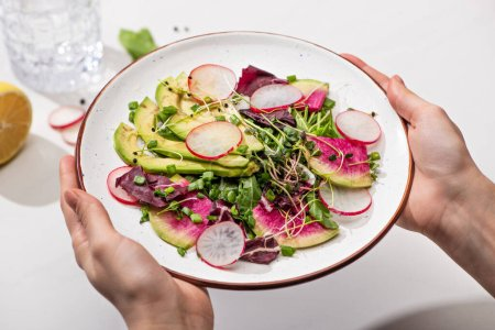 Photo for Cropped view of woman holding fresh radish salad with greens and avocado on plate - Royalty Free Image
