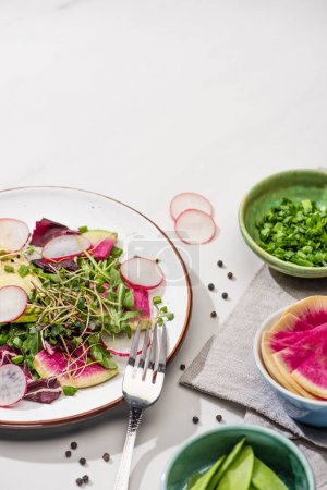 Photo for Fresh radish salad with greens and avocado on plate on white surface with ingredients in bowls and fork - Royalty Free Image