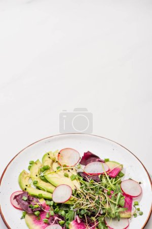 Photo for Fresh radish salad with greens and avocado on plate on white surface - Royalty Free Image