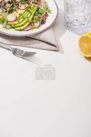 Photo pour Salade de radis frais avec légumes verts et avocat sur une surface blanche avec citron et eau - image libre de droit