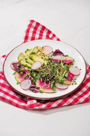 Photo pour Salade fraîche de radis avec légumes verts et avocat sur assiette à la surface blanche avec serviette - image libre de droit