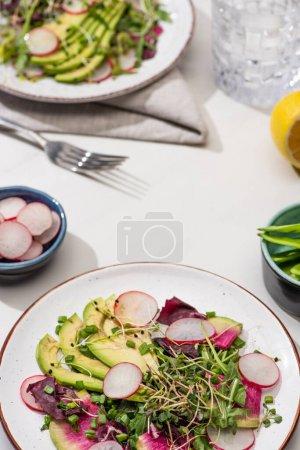 Photo pour Foyer sélectif de salade de radis frais avec des verts et de l'avocat sur la surface blanche - image libre de droit