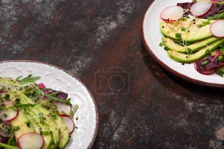 Foto de Ensalada de rábano fresco con verdura y aguacate en platos de superficie teñida. - Imagen libre de derechos