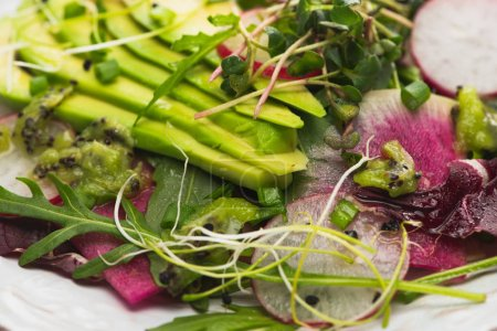 Photo for Close up view of fresh radish salad with greens and avocado - Royalty Free Image