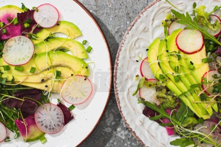 Photo for Top view of fresh radish salad with greens and avocado on plates on grey concrete surface - Royalty Free Image
