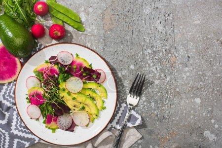 Photo pour Vue de dessus de la salade de radis frais avec légumes verts et avocats près de la fourchette et légumes sur la surface en béton gris - image libre de droit