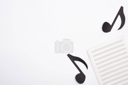 Photo pour Top view of music book and paper cut notes on white background - image libre de droit