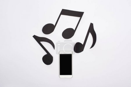Photo pour Top view of music paper cut notes and smartphone on white background - image libre de droit