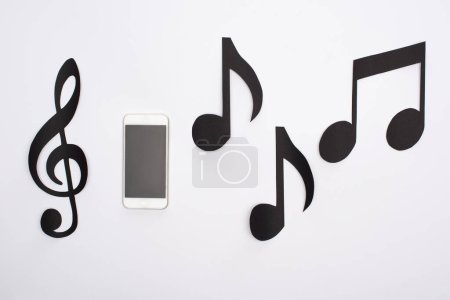 Photo pour Top view of paper cut music notes with smartphone on white background - image libre de droit