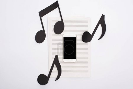 Photo pour Top view of smartphone with paper cut notes on music book on white background - image libre de droit