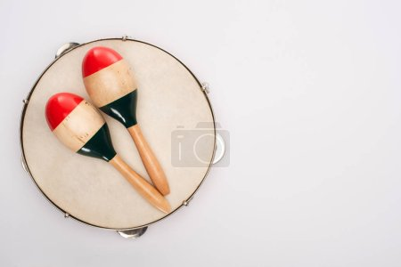 Photo pour Top view of wooden maracas on tambourine on white background - image libre de droit