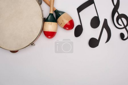 Photo pour Top view of wooden maracas near tambourine and paper cut music notes on white background - image libre de droit